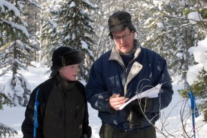 En man och en pojke tittar på en karta i den snöiga skogen.