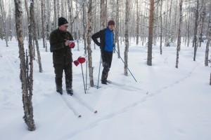 Två skidåkare tittar på en spårlöpa i den snöiga skogen.