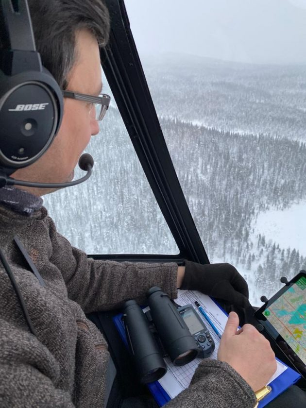 Mies istuu helikopterissa. Hänellä on sylissään kartta, GPS ja kiikarit.