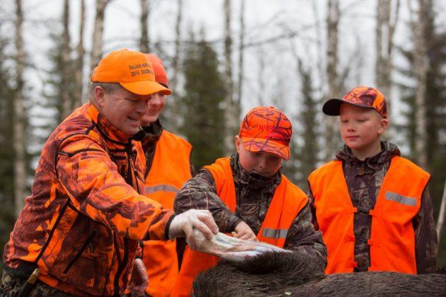 Neljä metsästäjää nylkee hirveä