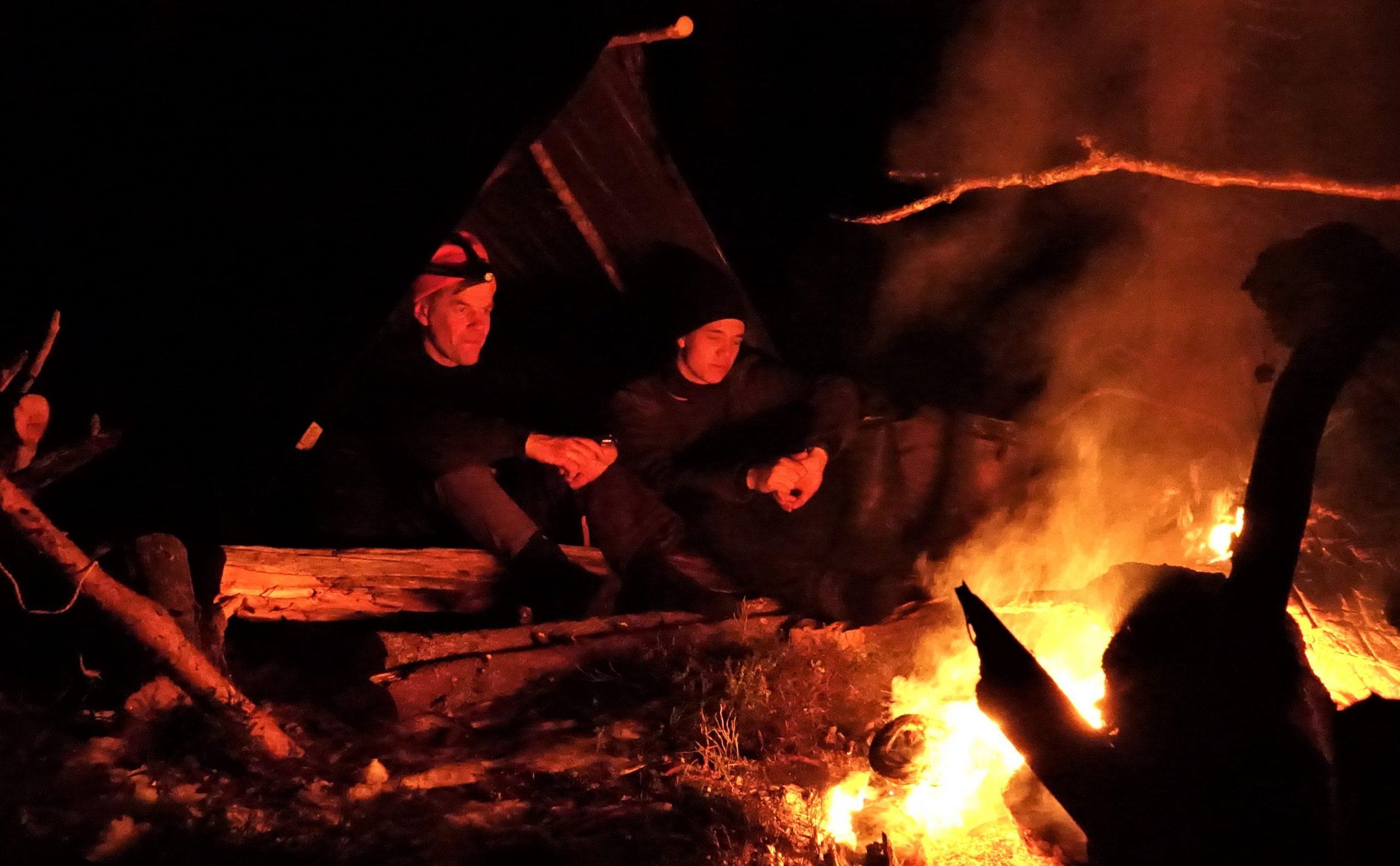 Kaksi ihmistä istumassa pimeän aikaan tulen äärellä.