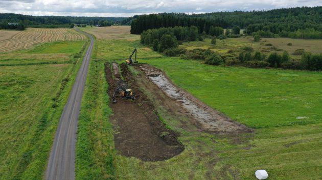 Kaksi kaivinkonetta on muokannut maata. Maisemassa peltoa, tie, nurmea ja kosteikkoa.