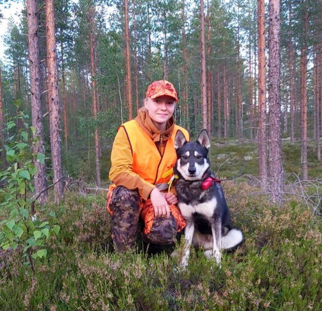 Huomioväreihin pukeutunut metsästäjä istuu varvikossa koira vierellään.