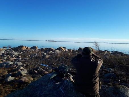 Kivikossa seisova metsästäjä tähyilemässä merelle.
